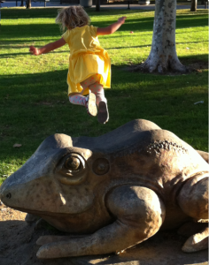 Leaping off a stone frog at the park